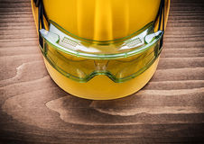 Safety spectacles and building helmet on wooden board constructi Royalty Free Stock Photography