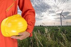 Safety suit and hand hold yellow helmet with Wind turbines generating electricity. energy conservation concept royalty free stock photos