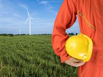 Safety suit and hand hold yellow helmet with Wind turbines generating electricity. energy conservation concept stock photography