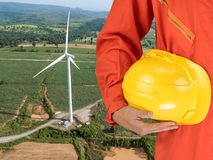 Safety suit and hand hold yellow helmet with Wind turbines generating electricity. energy conservation concept stock photos