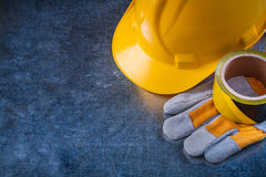 Safety tape hard hat and protective gloves on Stock Photography