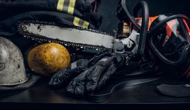 Safety unform on the table with respirator and chainsaw. Safety unform on the table -  jacket and gloves with oxygen cylinder, respirator and chainsaw. There royalty free stock image