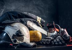 Safety unform on the table with respirator and chainsaw. Safety unform on the table -  jacket, helmet and gloves with oxygen cylinder and chainsaw. There are royalty free stock image