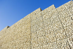 Safety wall. Made of stacked meshed boxes of stones Stock Photography