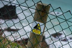 Safety warning sign on wooden post on cliff Royalty Free Stock Images