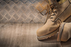 Safety waterproof lace boots wooden board channeled metal plate. Construction concept royalty free stock images
