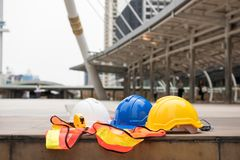 Engineer safety equipment at site. Safety white, blue, yellow helmet hats, measure tape, and worker dress on concrete floor at modern city with blurred people Stock Photos
