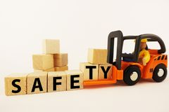 Safety at work concept with orange forklift with wooden blocks on white background royalty free stock photo