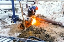 Safety at work. Welding and installation of the pipeline. Industrial weekdays welders and fitters. Safety at work. Welding and grinding of iron constructions stock photography