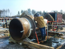 Safety at work. Welding and installation of the pipeline. Industrial weekdays welders and fitters. Safety at work. Welding and grinding of iron constructions stock photos