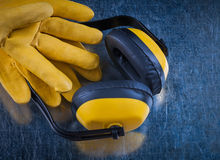 Safety yellow ear muffs and pair of leather construction gloves Stock Images
