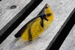 Safety yellow glasses on a wooden background. Glasses lie. Yellow glasses on a wooden background. Glasses lie. Black orange glasses stock photos