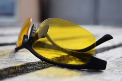 Safety yellow glasses on a wooden background. Glasses lie. Yellow glasses on a wooden background. Glasses lie. Black orange glasses stock images