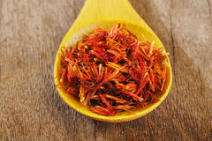 Safflower in wooden spoon Royalty Free Stock Image