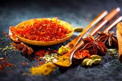 Saffraan Diverse Indische kruiden op zwarte steenlijst Kruid en kruiden op leiachtergrond stock foto's