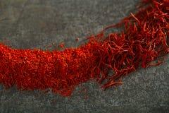 Saffranutrymmetrådar och pulver i metallbakgrund Royaltyfria Foton