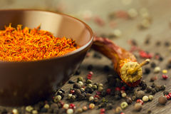 Saffron in brown bowl with chili and pepper Stock Image
