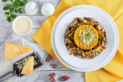 Saffron creamy risotto with fried porcini. Delicious saffron creamy risotto topped with fried porcini sprinkled with parsley and grated parmesan cheese served on Royalty Free Stock Photos