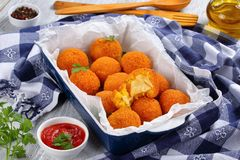 Saffron rice balls stuffed with cheese. Arancini - saffron rice balls stuffed with cheese in baking dish on old wooden table with kitchen towel, tomato sauce Royalty Free Stock Photography
