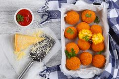 Saffron rice balls stuffed with cheese. Delicious deep fried sicilian arancini - saffron rice balls stuffed with cheese in baking dish on old wooden table with Royalty Free Stock Images