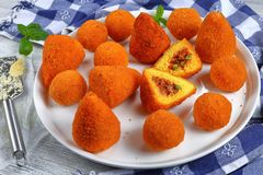 Saffron rice cone stuffed with meat. Sicilian arancini - saffron risotto cones and balls stuffed with meat ragu and green peas on platter on wooden table with Royalty Free Stock Photography