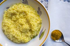 Saffron rice with a spoon of its principal ingredient. Flat lay of a dish of saffron rice with a spoon of the principal ingredient Royalty Free Stock Image