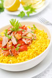 Saffron rice with tuna, tomatoes, peppers and greens close-up Royalty Free Stock Image