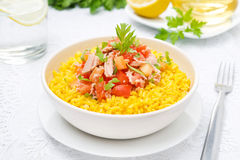 Saffron rice with tuna, tomatoes, peppers and herbs in a bowl Stock Image