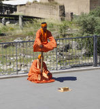 Saffron Robe clad street performers. Saffron Robed turban clad street performers perform a clever illusion of strength and meditation, hoping for some coins to Royalty Free Stock Photo