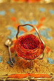 Saffron spice in antique vintage glass bowl, closeup Stock Images