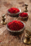 Saffron spice in antique vintage iron bowls weights stacked on w Royalty Free Stock Image