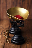 Saffron spice in antique vintage iron scale bowl on wooden table Stock Image