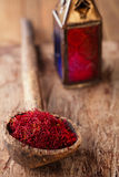Saffron spice in antique wooden spoon on old wood background, cl Royalty Free Stock Image