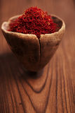 Saffron spice in antique wooden spoon on old wood background, cl Stock Photo