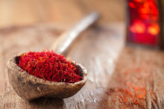 Saffron spice in antique wooden spoon on old wood background Royalty Free Stock Image