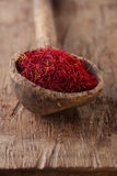 Saffron spice in antique wooden spoon on old wood Royalty Free Stock Photography