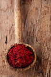 Saffron spice in antique wooden spoon on old wood background Stock Photo