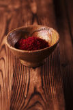 Saffron spice in earthenware bowl on old textured wooden backgro Stock Photos
