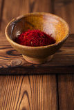 Saffron spice in earthenware bowl on old textured wooden backgro Royalty Free Stock Photography