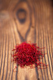 Saffron spice in pile on old textured wooden background. Closeup Royalty Free Stock Images