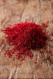 Saffron spice in pile on old wooden background Stock Images