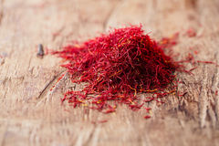 Saffron spice in pile on old wooden background Royalty Free Stock Images