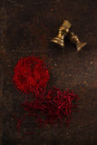 Saffron spice in pile threads and powder on old metal background Royalty Free Stock Photography