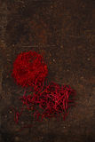 Saffron spice in pile threads and powder on old metal background Royalty Free Stock Photo