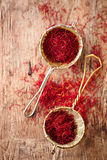 Saffron spice in rustic sieve on old wooden background. Closeup Stock Photos