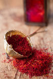 Saffron spice in rustic sieve on old wooden background Royalty Free Stock Images