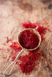 Saffron spice in rustic sieve on old wooden background Royalty Free Stock Photography