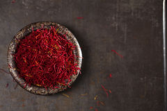 Saffron spice threads and powder  in vintage iron dish Royalty Free Stock Image