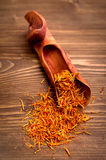 Saffron spice threads in scoop on wooden background Royalty Free Stock Photos