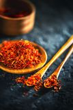 Saffron spices. Saffron on black stone table in a wood bowl and a spoon. Spice and herbs on slate background Stock Photo